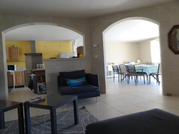 woonkamer met zithoek, open keuken en grote tafel voor 14 pers.
